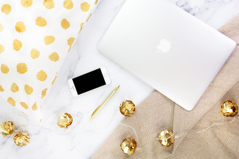 Laptop Handy und ein Kissen mit einer Lichterkette